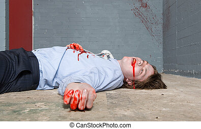 Murder victim lying on the floor, being shot in a basement, with blood splatter on the wall