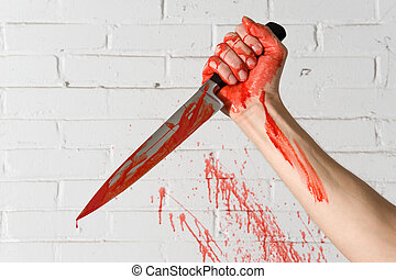 Murder weapon - Blood covered knife, still dripping, in the...