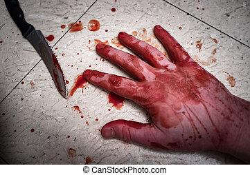 Crime scene murder victim hand with blood spatter on floor