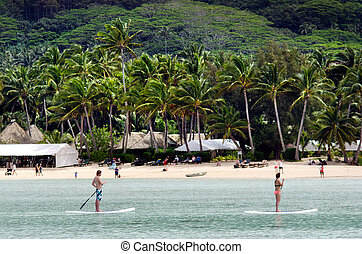 RAROTONGA - SEP 16:Man and a woman stand up paddle boarding over Muri Lagoon on Sep 16 2013.Cooks Islands are largely unspoiled by tourism with only 100,000 visitors a year.
