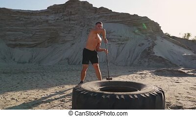 Muscle athlete strongman man hits a hammer on a huge wheel in the sandy mountains in slow motion. strength and endurance training for wrestlers