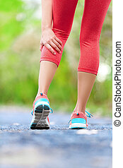 Muscle injury - woman running clutching calf muscle
