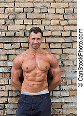 Muscle man on a brick wall background
