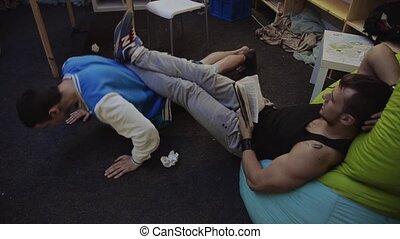 Muscle man read book on beanbag, keep legs on boy in sport...
