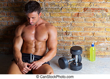 muscle man relaxed with weights and drink