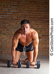 muscle shaped man on knees with training weights