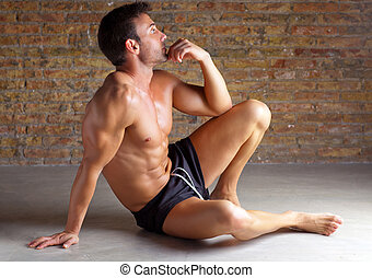 muscle shaped man sitting relaxed on brickwall - muscle...