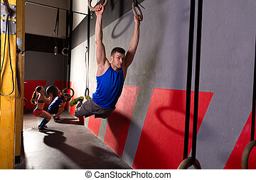 Muscle ups rings man swinging workout at gym