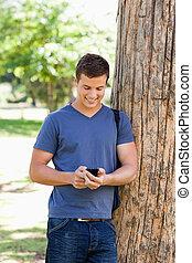muscled, junger mann, gebrauchend, a, smartphone