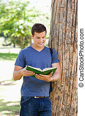 Muscled young man reading a book