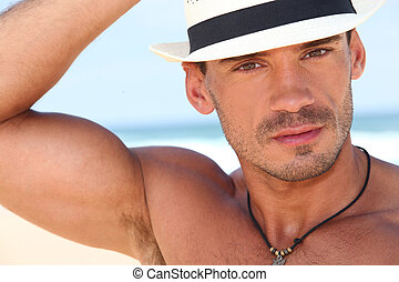 Muscled young man with a hat