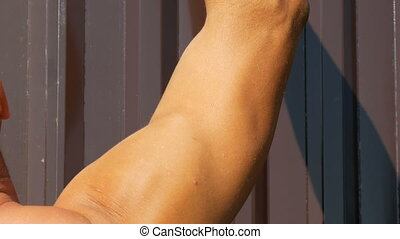 Muscles of young tanned worker who works with tools. Young...