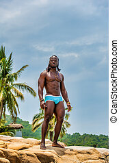 Muscular African American Man Standing on a Rock
