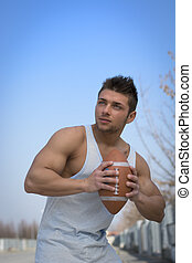 Muscular american football player ready to throw ball