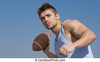 Muscular american football player ready to throw ball in ...