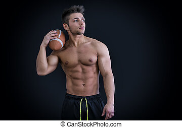 Muscular american football player standing with ball in...