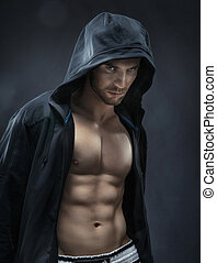Muscular and handsome athlete making muscles - Muscular and...