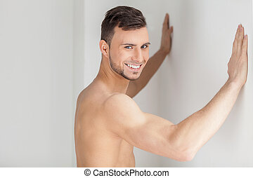 Muscular and handsome. Handsome young muscular man leaning at the wall and looking at camera