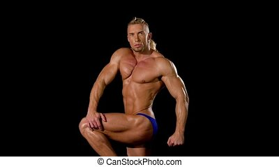 Muscular and sexy torso of young man posing sitting, bodybulider isolatedon black