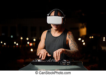 Muscular and tattooed nightclub DJ in night vision glasses