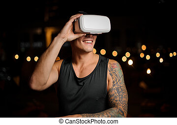 Muscular and tattooed smiling handsome man in night vision glasses