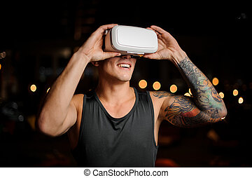 Muscular and tattooed smiling handsome man looks in night vision glasses