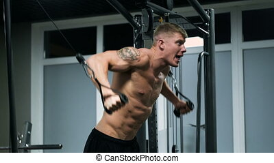 Muscular athlete in the gym, doing heavy exercise.