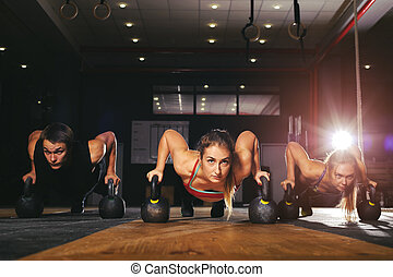 Muscular athletes doing push ups with kettlebell