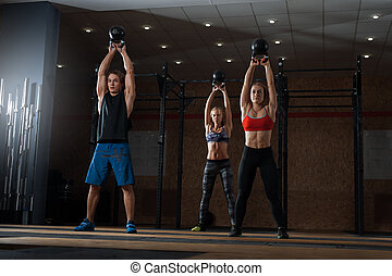 Muscular athletes exercising with kettle bell