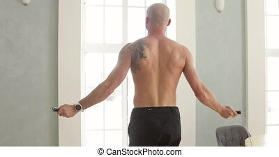 Muscular athletic man is jumping rope making cardio training at home in kitchen, back view. Skipping rope. Sport and fitness. Workout and wellness concept. High-intensity interval training.