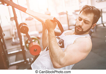 Muscular Bearded man during workout in the gym.