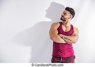 muscular, bodybuilder, apoiando, parede branca