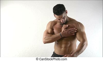 Muscular bodybuilder Applying Oil to his Skin - Handsome...