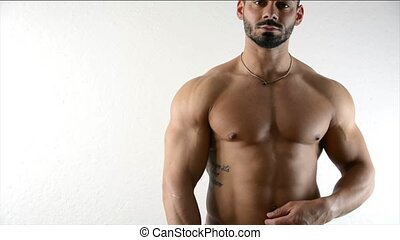 Muscular bodybuilder by white wall - Muscular bodybuilder by...
