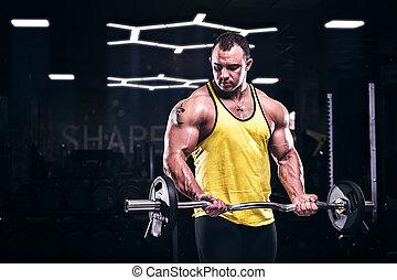 Muscular bodybuilder doing biceps exercise in gym