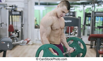 muscular bodybuilder makes exercise for biceps in the gym -...