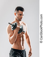 Muscular bodybuilder man doing exercises with dumbbell