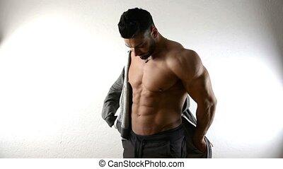 Muscular bodybuilder man dressing, putting on jacket