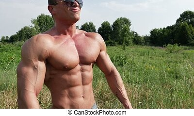 Muscular bodybuilder man shirtless in lawn