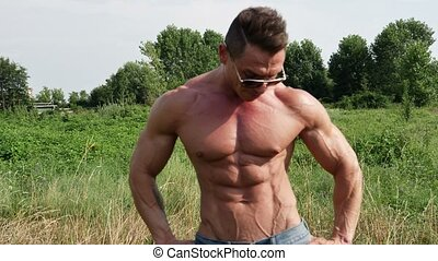 Muscular bodybuilder man shirtless in lawn - Muscular...