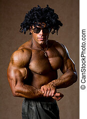 Muscular bodybuilder with curly hair shows his biceps