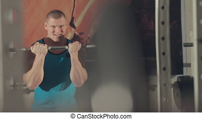 Muscular bodybuilder work out with heavy barbell in gym in front of the mirror