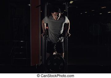 Muscular bodybuilder working out in gym doing exercises on parallel bars.
