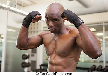 Muscular boxer in defensive stance in health club