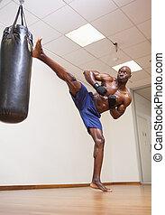Muscular boxer kicking punching bag