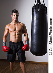 Muscular boxer with punching bag in gym