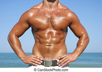 A man with a beautiful muscular body relaxing on the beach