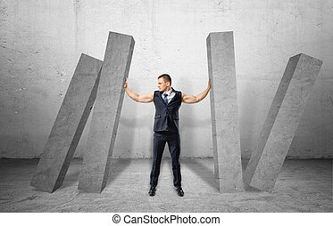 Muscular businessman full-height holding concrete four columns falling on him