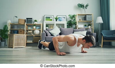 Muscular dark-haired guy doing pushup working out at home in...