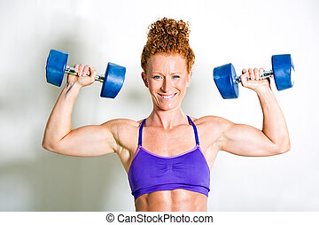Muscular female athlete pressing dumbbell weights